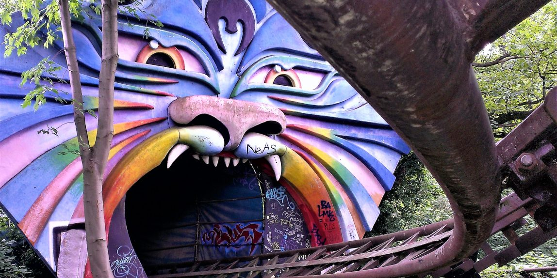 An abandones rollercoaster in shape of a dragon in all the colours of rainbow with an open mouth and scary teeth